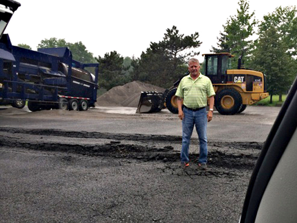 Lewiston Supervisor Dennis Brochey stands in the holes of the failed parking lot at Joe Davis Park. Behind him are Suit-Kote trucks which some say caused the broken lot.